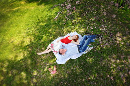 loving couples: couple relaxing on the grass in the blossoming spring garden. Stock Photo