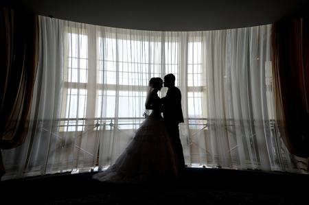 parejas romanticas: Silueta de la novia y el novio se besan delante de la ventana estrecha. Foto de archivo