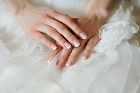 marido y mujer: manos de la novia con una manicura en su vestido de primer plano Foto de archivo