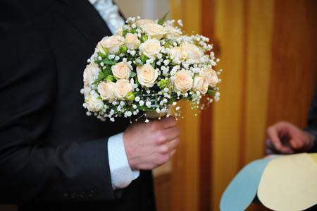 marido y mujer: ramo de la boda con flores en las manos del novio.