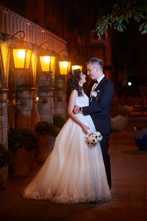 wedding bride: bride and groom walk in city at night.