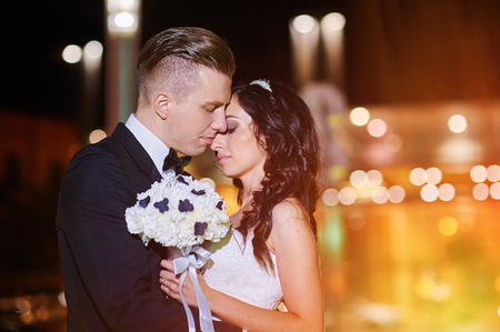 bride and groom background: bride and groom walk in city at night.
