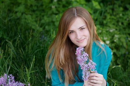 flor violeta: hermosa mujer con un ramo de lilas en el jardín de primavera.