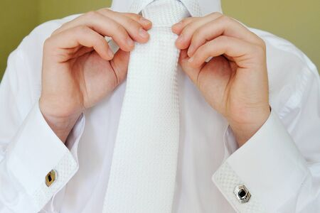 correcting: Detail of young businessman correcting a white tie.
