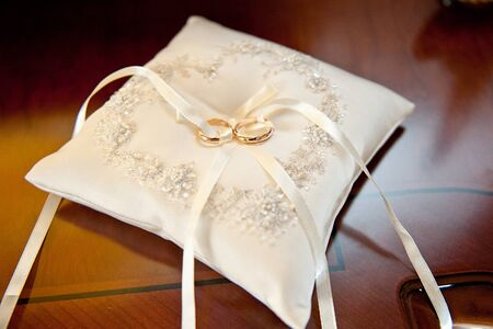 nuptials: Two amazing golden shiny rings jewel for nuptials ceremony laying on white beautiful pillow with bow.
