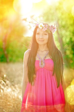 flower head: Attractive young woman with flower wreath on her head with sunset in background. Stock Photo