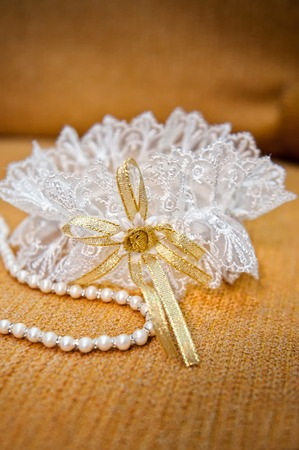 garter: Elegant bride garter and pearls necklace in wedding day Stock Photo