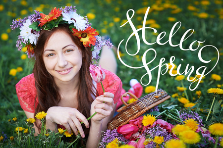 Beautiful happy young woman enjoying smell in a flowering spring garden with letters Hello sprint Stock Photo