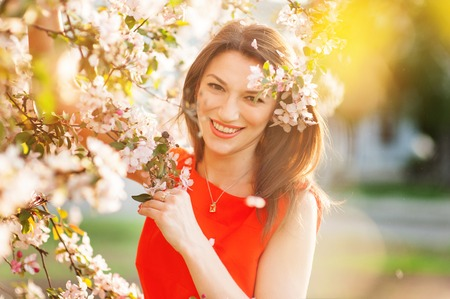 Sensual portrait of spring woman, beautiful face female enjoying cherry blossom, tree branch and glamorous lady