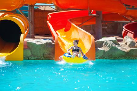 아름 다운 젊은 여자 물 공원에서 슬라이드를 당긴 다.