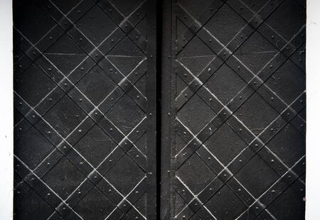 old metal: texture of black old metal door with rivets for background.