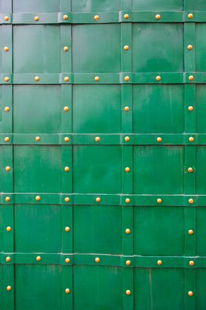 rivets: texture of green old metal door with rivets for background. Stock Photo