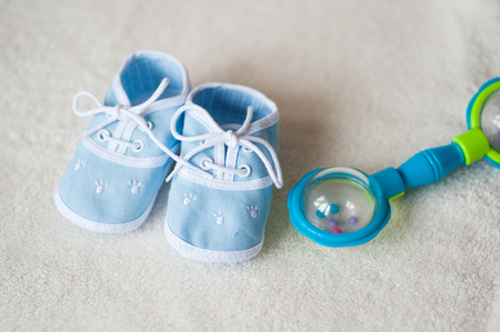 blue baby shoes and rattle on light background