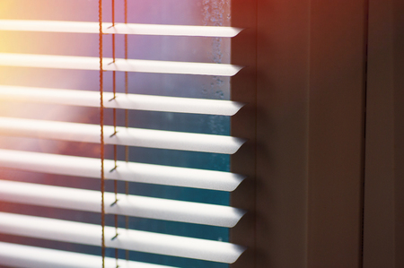 blind: Sunlight coming through venetian blinds by the window.