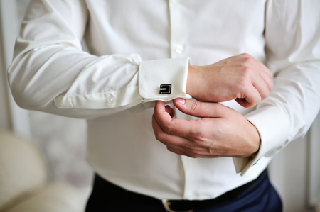 wrist cuffs: man wear a white shirt and cufflinks