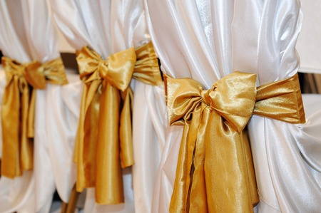 wedding chairs: Wedding chairs in row decorated with golden color ribbon. Stock Photo