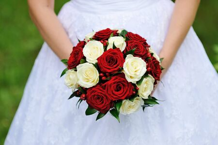 red and white wedding bouquet of roses in the hands of the bride Foto de archivo