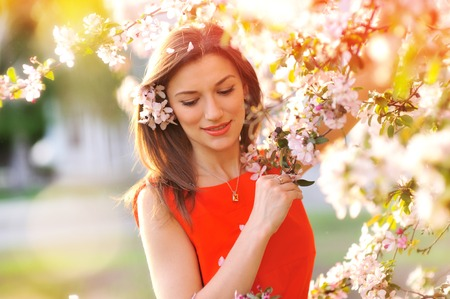 Beautiful Spring woman with blossoming flowers on trees in garden. Stockfoto