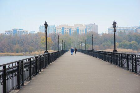 Bridge with lanterns along the river on background of city. Фото со стока