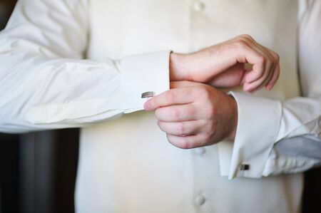 cuffs: groom in the morning on the wedding day buttoning cuffs his hands. Stock Photo