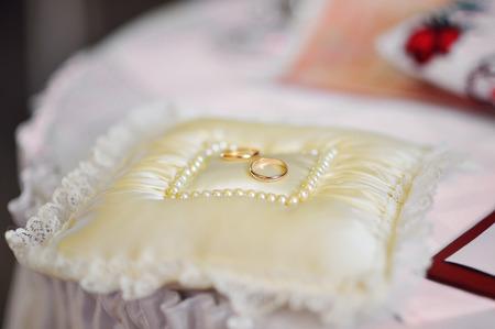 bearer: golden wedding rings on white ring bearer pillow.