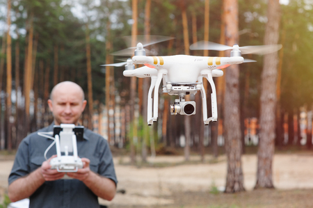 unmanned: Man using his drone outdoor with forest background.
