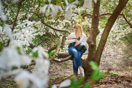interested baby: Mom with a baby boy sitting on a tree branch in the flowered spring garden.