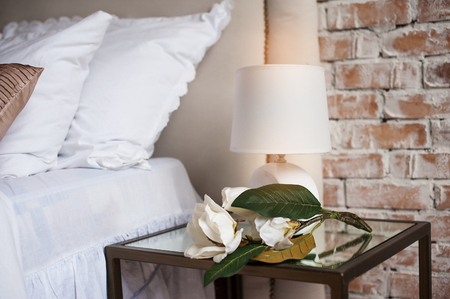 bedside lamp: Comfortable and serene bedside with lamp by the bed.