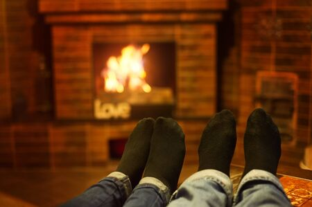 fireplace family: male and female legs near the fireplace. Family concept.