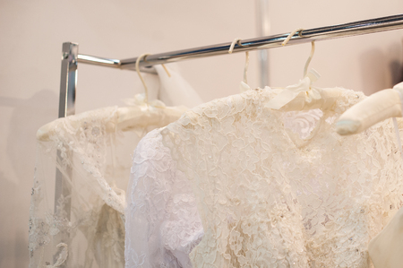 trample: Beautiful white cream wedding dresses made of silk chiffon, tulle and lace hanging on hangers with bows
