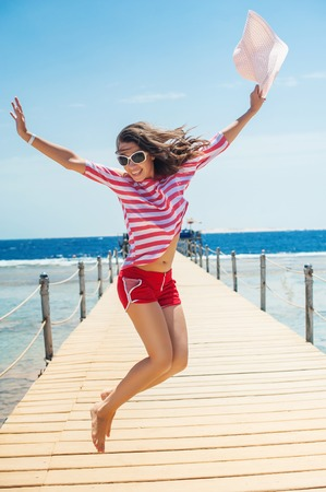 young woman full of energy jumping on a pontoon in front of the sea on a sunny day. Foto de archivo