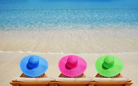 Tre donne sulla spiaggia in cappelli luminosi che viaggiano in vacanza.