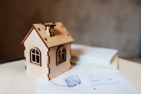 wooden toy: Real estate concept wooden toy house with paper diagram.