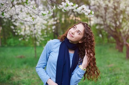 light complexion: young woman in the blossoming spring garden walks. Stock Photo