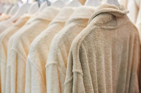 나무 옷장에 걸려 많은 흰색 목욕 가운.