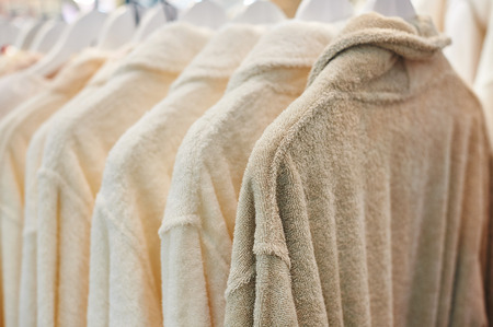 many white bathrobes hanging in wooden closet.