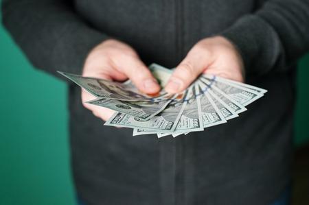 richer: man hand giving 100 dollar bills in studio.