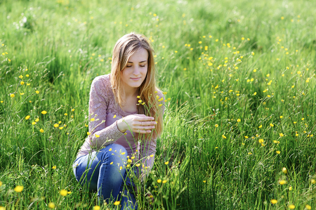 young woman picking flowers on a summer meadow. Foto de archivo