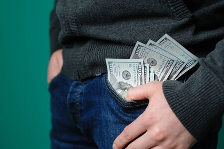 putting money in pocket: man putting a one hundred dollar banknotes into the chest pocket. Concept of earning money. Stock Photo