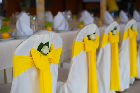 a meeting with a view to marriage: chairs with yellow bows on the wedding dinner. Stock Photo