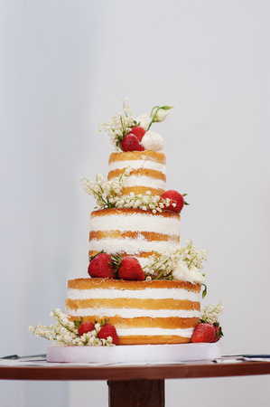 three-tiered wedding cake with strawberries on table. Foto de archivo