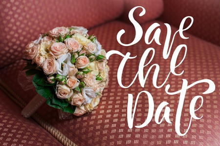 romantic date: Beautiful wedding bouquet of roses lying on the sofa words save the data. Stock Photo