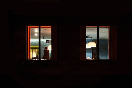 woman sitting in a lighted room near window at night.