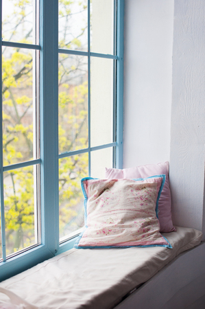 sill: Two pillows airing on window sill in room.