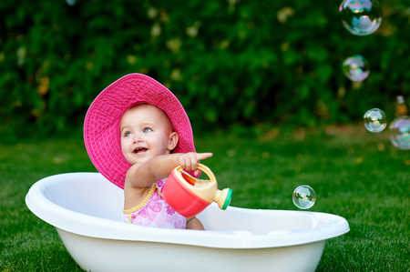 bathwater: little girl bathes in a bath with soap bubbles. Stock Photo