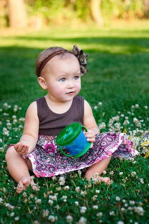 poquito: niña sentada en el césped y come galletas. Foto de archivo