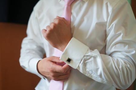cuffs: man puts on his shirt cuffs Morning groom Accessories. Stock Photo
