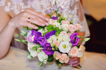 arm bouquet: Bride hand with gold ring a wedding bouquet on table.