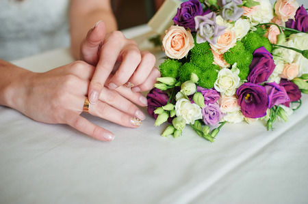 Bride hand with gold ring a wedding bouquet on table.