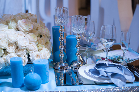 blue candles: Wedding decor in blue. candles and flowers on the table. Stock Photo